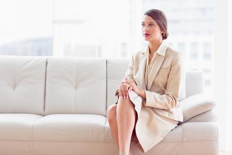 Thoughtful businesswoman sitting on sofaの写真素材 [FYI00000945]
