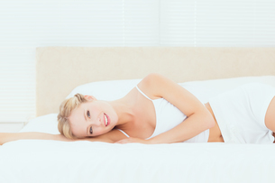 Pretty blonde lying on her bed smiling at cameraの写真素材 [FYI00000947]