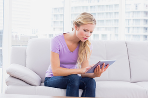 Beautiful blonde sitting on her sofa using her tablet pcの写真素材 [FYI00000948]