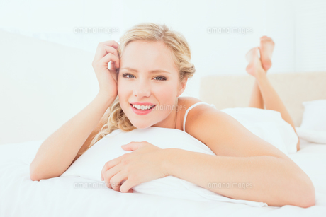 Natural young blonde lying on her bed smiling at cameraの素材 [FYI00000949]