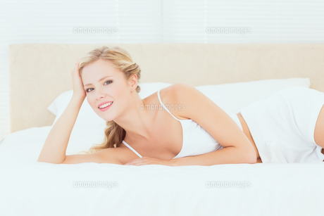 Attractive blonde lying on her bed smiling at cameraの素材 [FYI00000950]