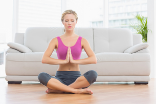 Calm blonde sitting in lotus pose with hands togetherの素材 [FYI00000951]