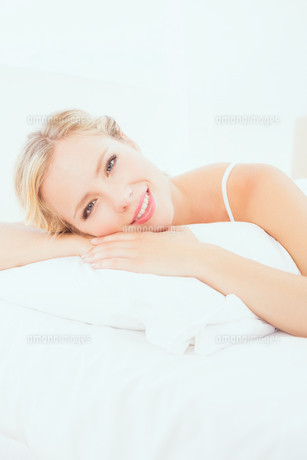 Cheerful young blonde lying on her bed smiling at cameraの素材 [FYI00000952]