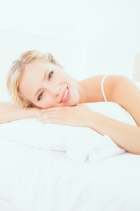 Cheerful young blonde lying on her bed smiling at cameraの写真素材 [FYI00000952]