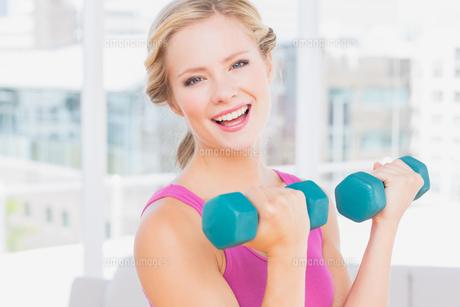 Happy blonde lifting dumbbells smiling at cameraの素材 [FYI00000953]