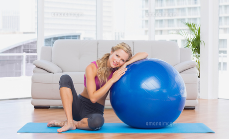 Toned blonde sitting beside exercise ball smiling at cameraの写真素材 [FYI00000954]