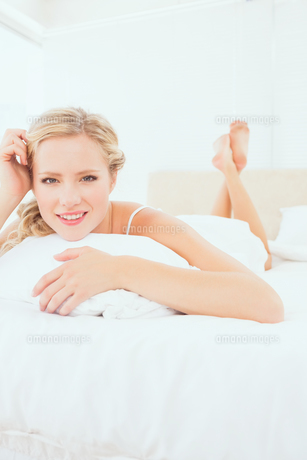 Content young blonde lying on her bed smiling at cameraの写真素材 [FYI00000955]