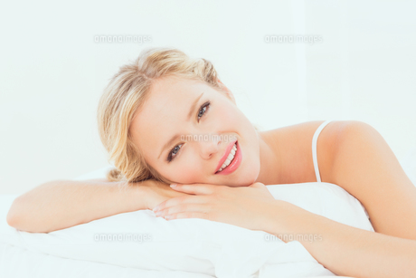 Attractive young blonde lying on her bed smiling at cameraの素材 [FYI00000959]