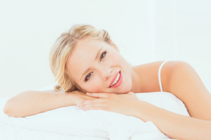 Attractive young blonde lying on her bed smiling at cameraの写真素材 [FYI00000959]
