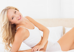 Attractive blonde woman lying on bed smiling at cameraの写真素材 [FYI00000965]