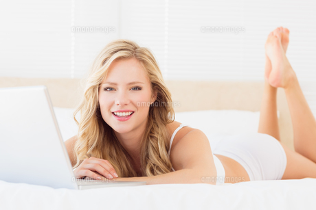 Smiling young blonde using her laptop on bedの素材 [FYI00000966]
