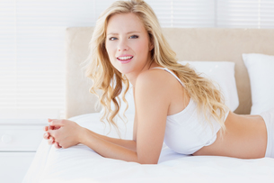 Happy young blonde woman smiling at camera on her bedの写真素材 [FYI00000968]