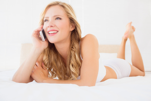 Happy young blonde on the phone lying on bedの素材 [FYI00000971]