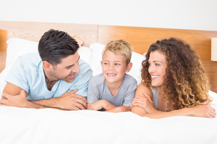 Happy young family lying on bed looking at each otherの写真素材 [FYI00000981]