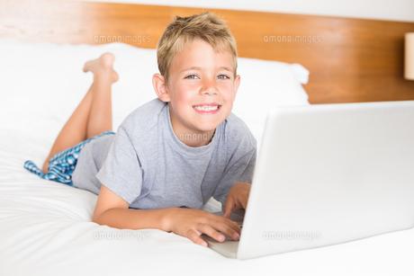 Happy blonde boy lying on bed using laptopの素材 [FYI00000983]