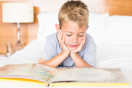 Happy blonde boy lying on bed reading a storybookの素材 [FYI00000984]