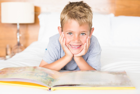 Smiling blonde boy lying on bed reading a storybookの素材 [FYI00000987]