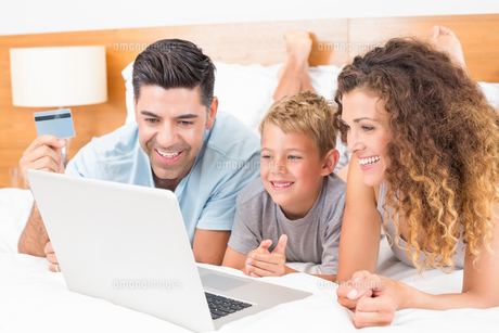 Happy young family using laptop to shop online together on bedの素材 [FYI00000988]