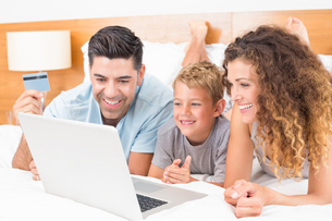 Happy young family using laptop to shop online together on bedの写真素材 [FYI00000988]