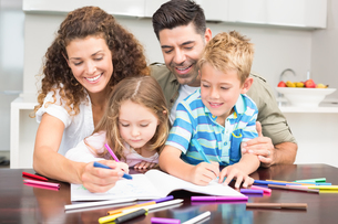 Happy parents colouring with their children at the tableの写真素材 [FYI00000991]
