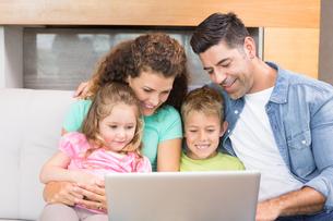 Happy family sitting on sofa using laptop togetherの素材 [FYI00000995]