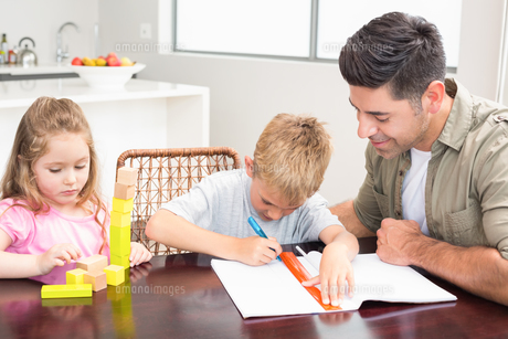 Father helping son with homework with little girl playing with blocksの素材 [FYI00000996]
