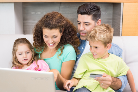 Cheerful family sitting on sofa with laptop shopping onlineの素材 [FYI00001003]