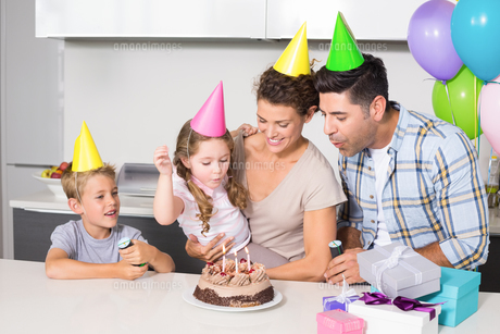 Happy young family celebrating a birthday togetherの写真素材 [FYI00001004]