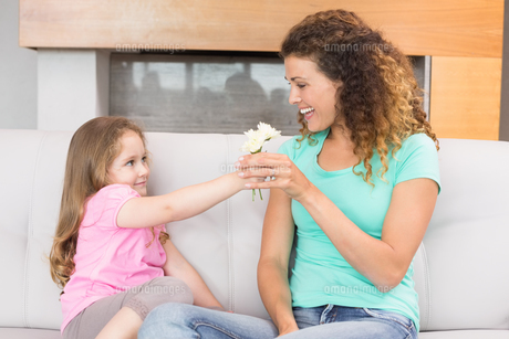 Smiling mother getting little flowers from her daughterの写真素材 [FYI00001006]