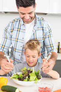 Smiling father tossing salad with his sonの写真素材 [FYI00001007]