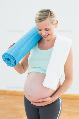 Pregnant blonde smiling at bump holding exercise matの写真素材 [FYI00001009]