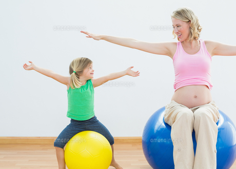 Pregnant woman bouncing on exercise ball with young daughterの写真素材 [FYI00001011]
