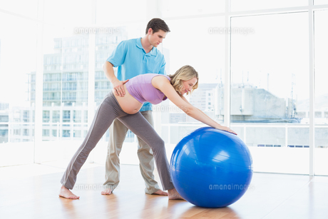 Trainer exercising with blonde pregnant client and exercise ballの写真素材 [FYI00001022]
