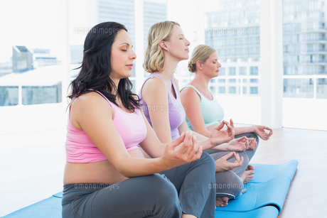 Relaxed pregnant women meditating in yoga classの素材 [FYI00001023]