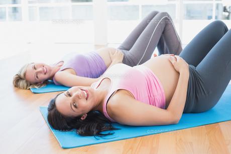 Smiling pregnant women in yoga class lying on matsの素材 [FYI00001024]