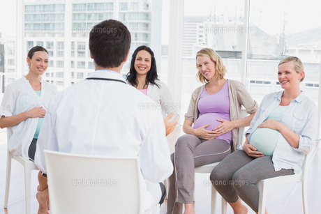 Smiling pregnant women listening to doctor at antenatal classの素材 [FYI00001025]