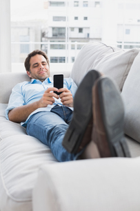 Happy man lying on the couch sending a textの写真素材 [FYI00001027]