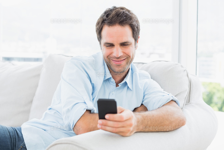 Happy man sitting on the couch sending a textの素材 [FYI00001029]