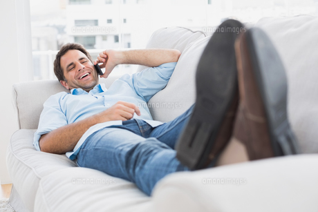 Happy man lying on the couch chatting on the phoneの素材 [FYI00001033]