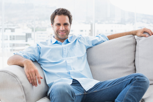 Happy handsome man relaxing on the couch looking at cameraの写真素材 [FYI00001034]