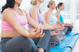 Calm pregnant women meditating in yoga classの写真素材 [FYI00001038]