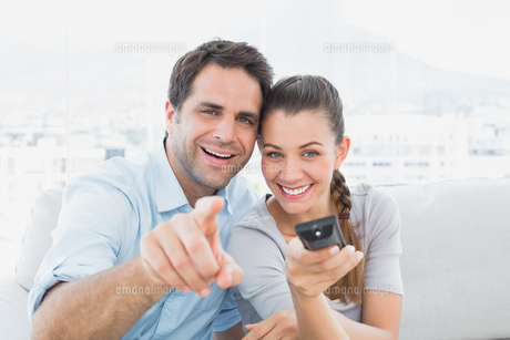 Smiling couple watching tv on the couchの写真素材 [FYI00001040]