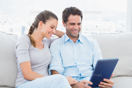 Smiling couple sitting on the couch using tablet pcの素材 [FYI00001045]