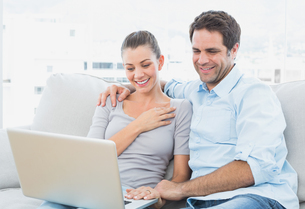 Cute couple sitting on the couch using laptop togetherの写真素材 [FYI00001047]