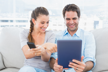 Happy couple sitting on the couch using tablet pc and watching tvの素材 [FYI00001048]