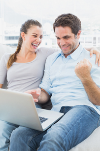 Excited couple sitting on the couch using laptop togetherの写真素材 [FYI00001049]
