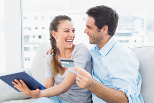 Laughing couple sitting on the couch shopping online with tablet pcの写真素材 [FYI00001050]