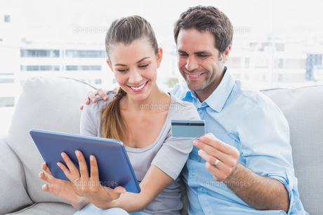 Happy couple relaxing on the couch shopping online with tablet pcの写真素材 [FYI00001051]