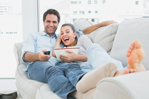 Couple watching funny movie lying on the sofa with bowl of popcornの写真素材 [FYI00001052]