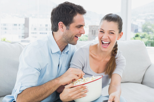 Couple watching funny movie on the sofa with bowl of popcornの写真素材 [FYI00001053]